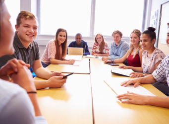 College Students Sitting At Table Having Discussion