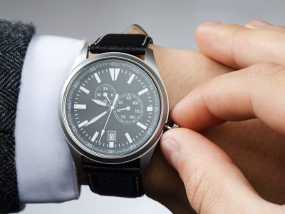 businessman adjusts the time on his wristwatch